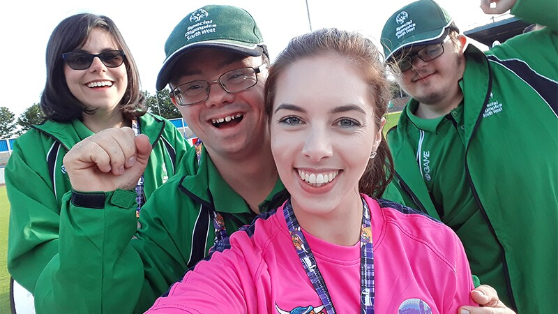 Three athletes and a Special Olympics representatives pose for a group selfie.