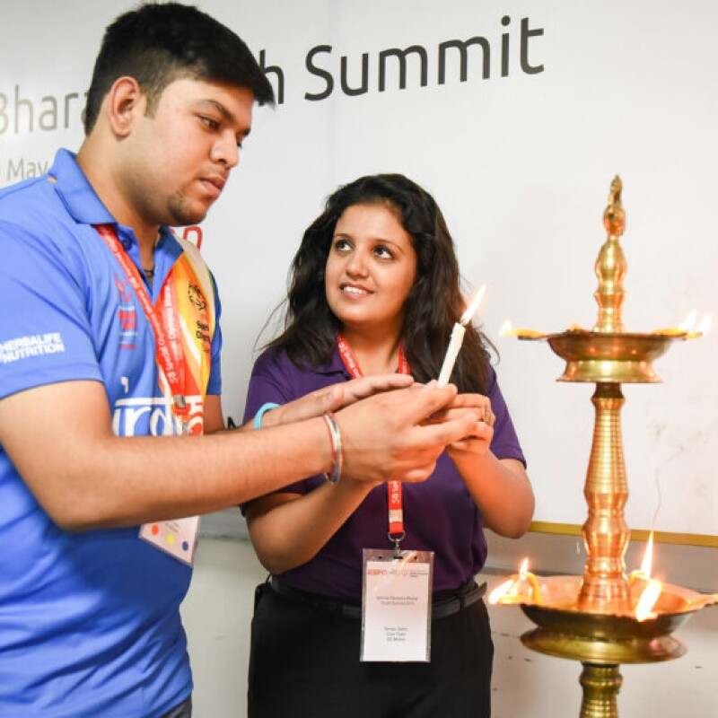 Young man and young woman lighting candles and putting them in a decorative candle holder.