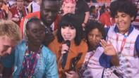 Female singer singing with athletes around her.