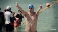 A swimmer with a blue swim cap coming out of the water and giving a thumbs up.