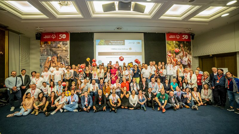Around 100 conference participants gathered in front of a large screen and Special Olympics branding.