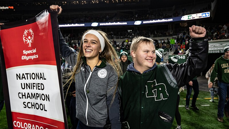 Two students on a field one is holding a banner that reads: Special Olympics National Unified Champion School