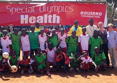 A group of athletes and Special Olympics representatives standing together in a group. The banner in the background reads: Special Olympics Health   Golisano Foundatoin