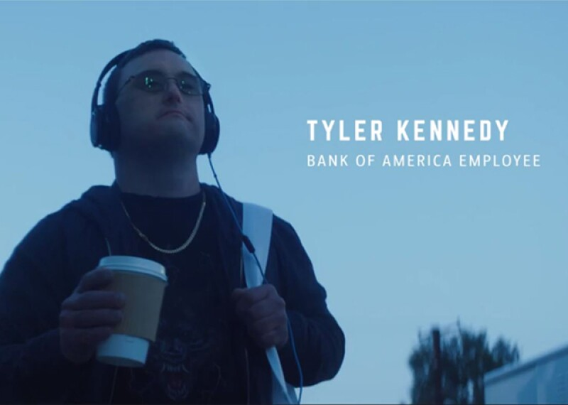 Tyler Kennedy walking down the street in a sweater with his back back and earphones on holding a cup of coffee.