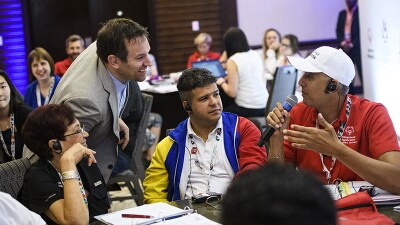 Dominican Republic representative speaking to a group of athletes and representatives.