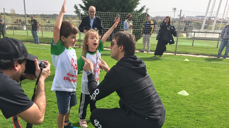 A man in a black tracksuit crouches on a green pitch, pointing at two young children in jerseys who are holding their hands in the air.