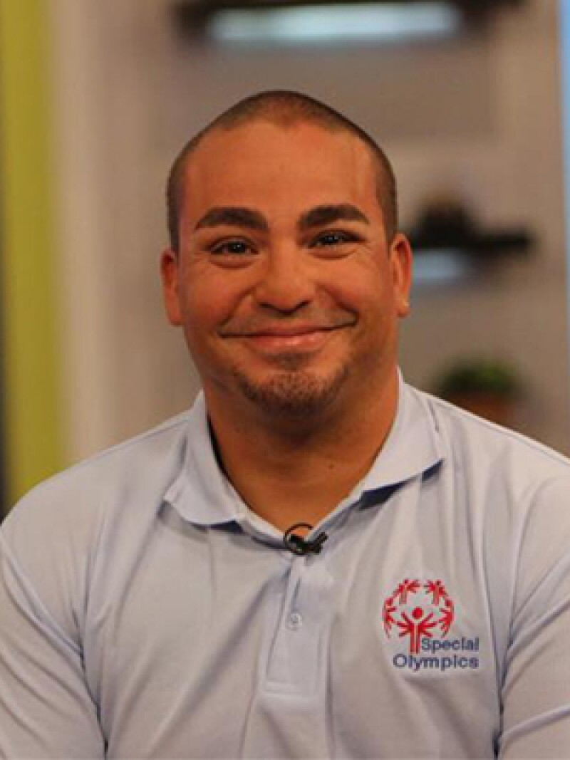 Joel Matos, smiling to the camera, wearing his Special Olympics polo shirt.