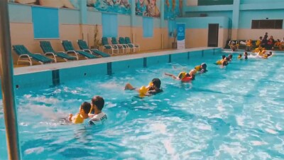 A small group of athletes swimming in the pool each with the assistance of an instructor.