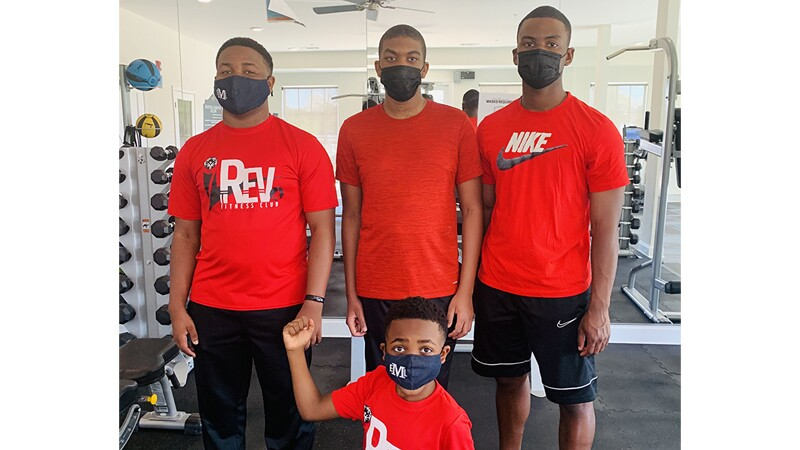Eric and his family members pose together inside a gym.