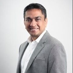 Seshasaye Kanthamraju in a gray suite and white button up shirt.