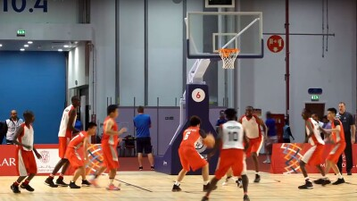 Two basketball teams on the court, one in red and white and the other in orange and white.