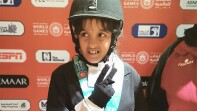 Sara Mashabek giving the peace sign in her equestrian outfit.