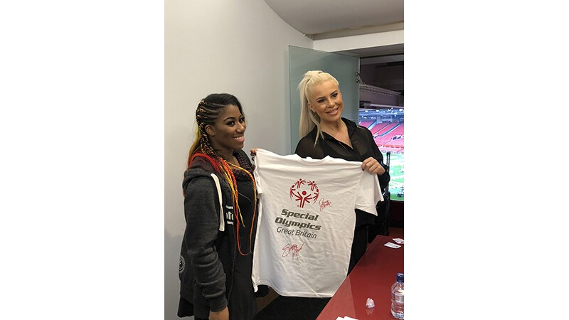WWE Superstars Ember Moon & Dana Brooke hold up a white Special Olympics Great Britain t-shirt they both signed.