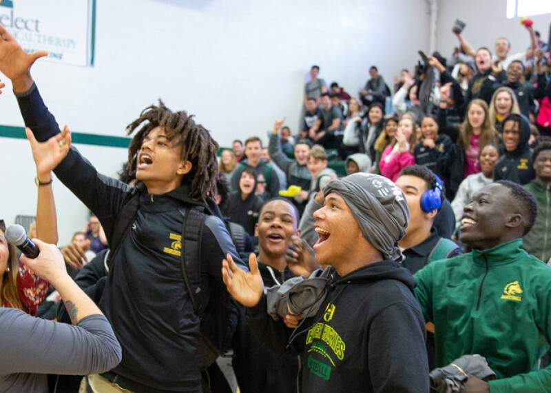 An image of an energetic school assembly. A young man in the front is reaching for a baton while other young adults cheer.