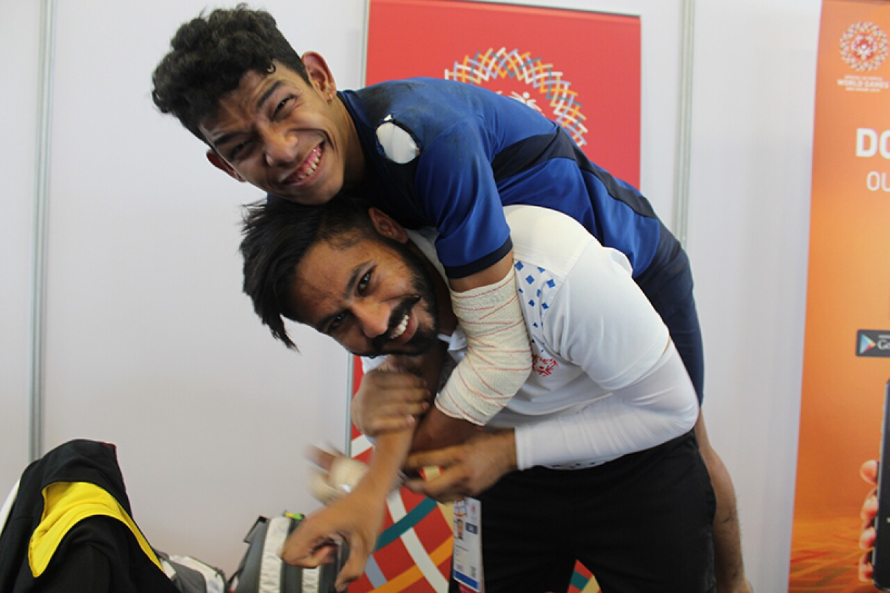 Abhishek with his unified partner goofing around; Abhishek jumping on his partners back.
