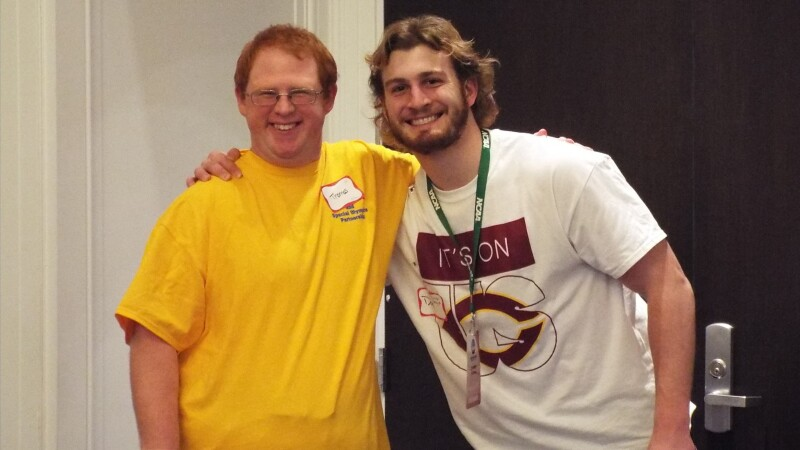 A Special Olympics athlete wearing a yellow shirt smiles at the camera. His arm is around a volunteer's shoulders.