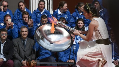Girl kneeling down and lighting flame of hope from the reflective dish, athletes and spectators are in the background.