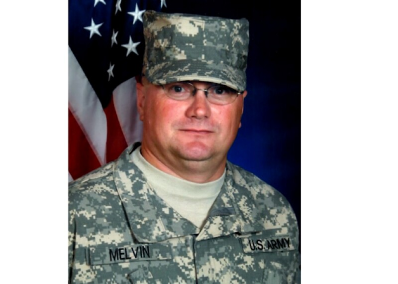 Ken Melvin in is US Army camouflage uniform sitting for his photo in front of the american flag.
