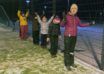 Five young women stand in a row on snow-covered grass next to a fence, with their arms up