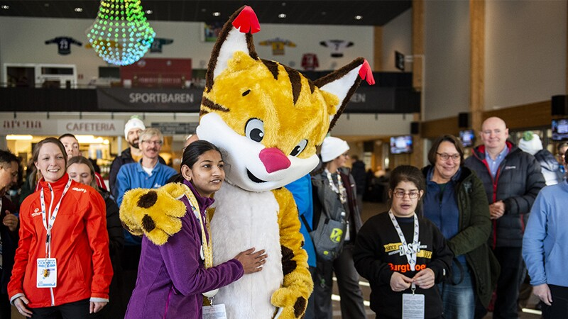 Speed Skater, Rachna, standing next to the cat mascot from the Sweden Invitational Games posing for a photo together while people stand around them and look on.