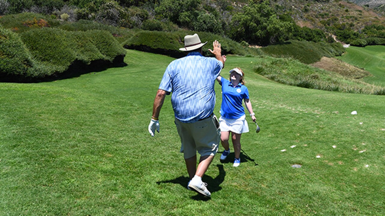 Amy high fives her triumph with celebrity golfer.