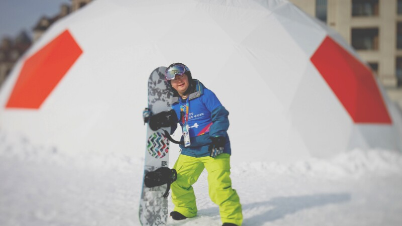 Athlete on the snow holding his board.