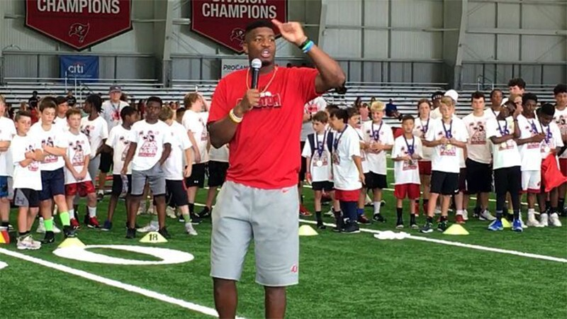 James Winston, NFL, Tampa Bay Buccaneers Quarterback on the field speaking into the microphone with young kids behind him.