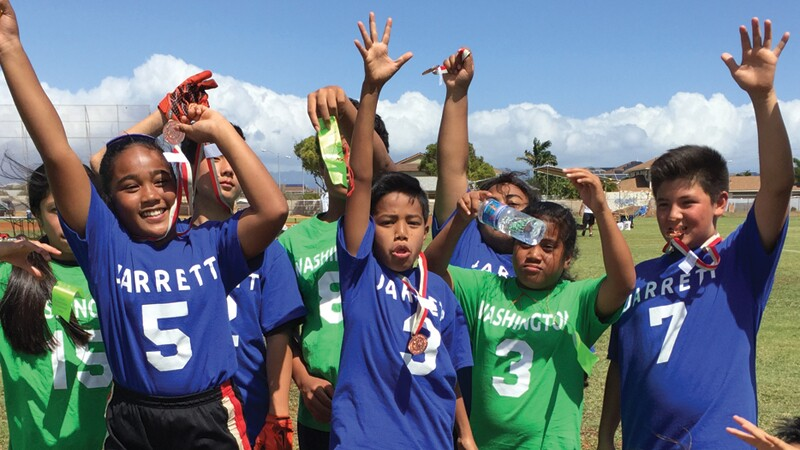 Jarrett Middle vs Washington Middle students in Hawaii together in a small group in a field.