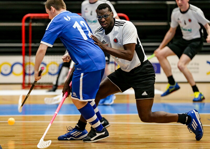 Floorball players in the middle of a game.
