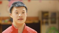 Xiang Li in a red athletic zip up.