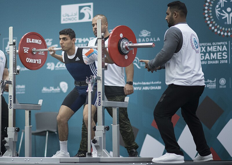 Athlete lifting weights on his shoulders. A spotter on either side and behind him.