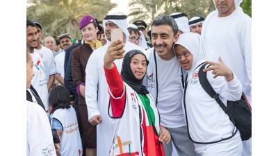 H.H. Sheikh Abdullah poses for a selfie with two Special Olympics Abu Dhabi athletes.