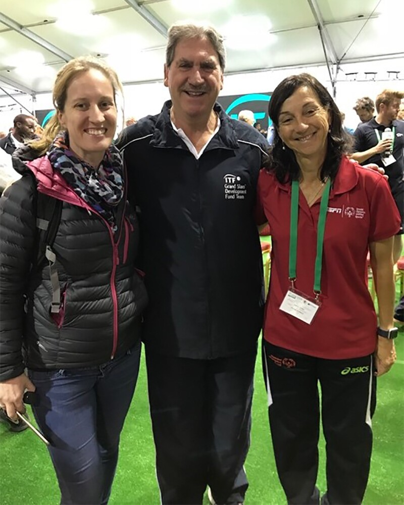 Coach Maria standing with David Hagherty and Fiona Murry in a venue.