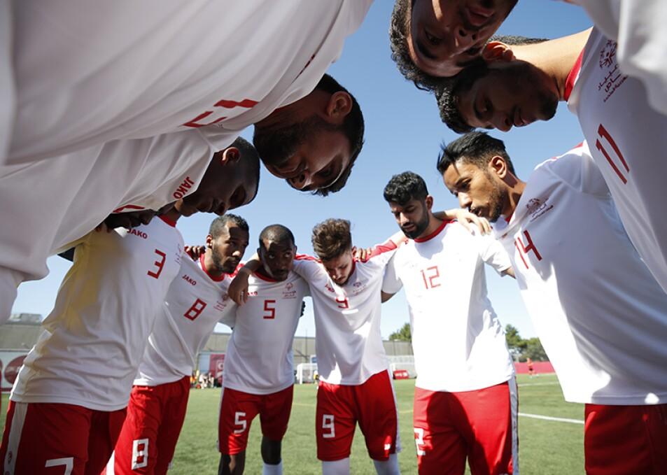Men's UAE teammates huddle together on the field.