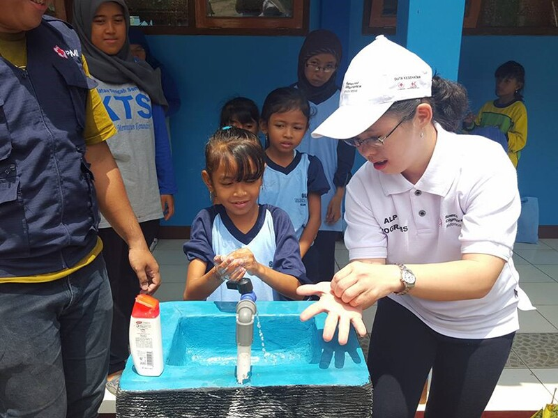 Young woman shows a young girl how to properly wash her hands while other young girls look on.