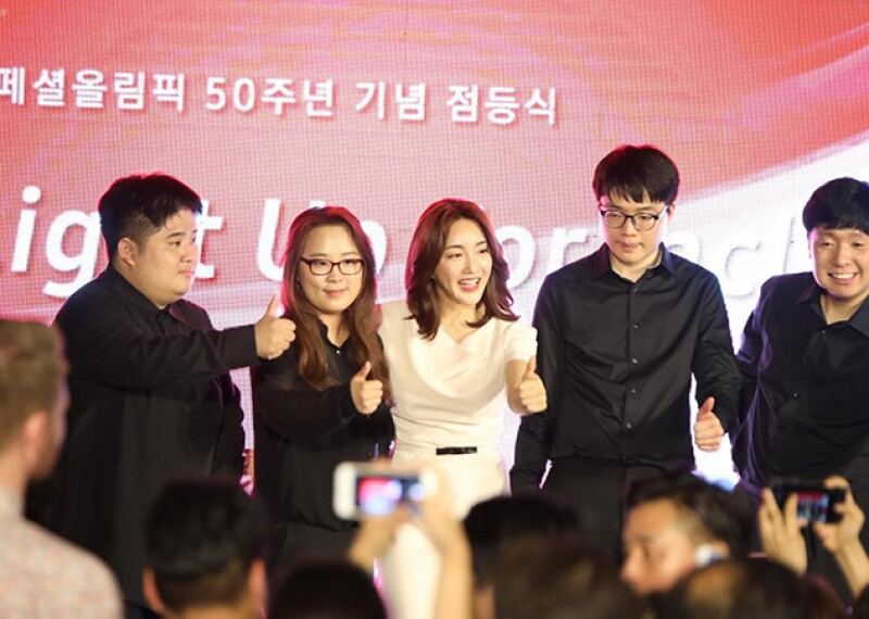"""Singer Bada in an off white dress and a group of four supports (one female and three male) dressed in all black on stage in front of a light up sign that reads """"Light up for Inclusion."""""""