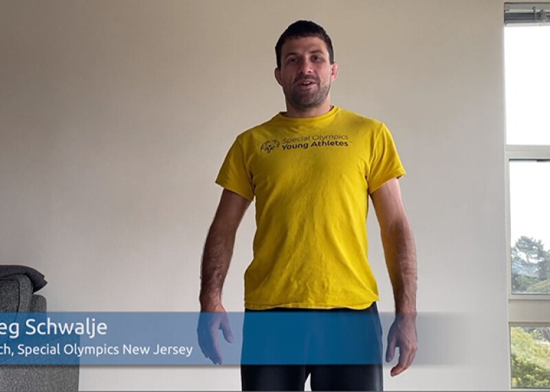 Coach Greg from Special Olympics New Jersey staging in a living room wearing a yellow Special Olympics Young Athletes t-shirt.