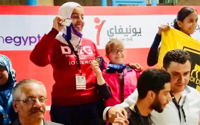 Two young women stand on a podium, smiling, holding medals in the air, with other medalists standing around then.