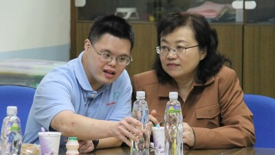 Michael Fan (left) and his mother Angela Huang (right) sitting at a table during a presentation.