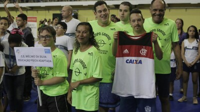 A group of six wearing matching lime green jerseys smiles, holding a sign with their school's name, and a football jersey. They are in a large gymnasium filled with people.