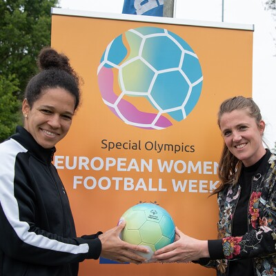 Two women holding a football in front of orange signage that reads, Special Olympics European Women's Football Week.