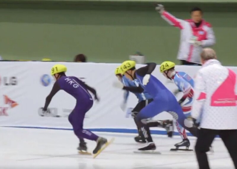 Speedskaters taking off and officials observing