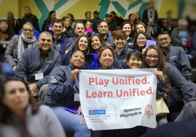 A group of people sitting in a sports stand face the camera holding up a white banner with the words 'Play Unified. Learn Unified' and the logos of Special Olympics and the Stavros Niarchos Foundation.