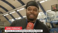 Sam Perkins being interviewed, he's holding a microphone and speaking to the camera.