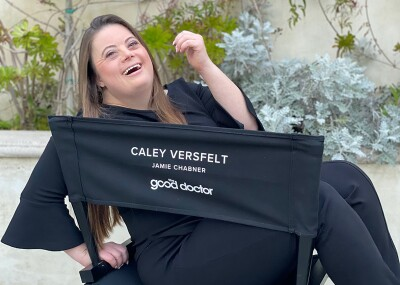 Caley Versfelt sits a director's style chair with her name on it of The Good Doctor with a smile on her face.