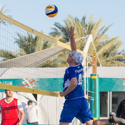 Beach Volleyball player jumping to spike the ball.