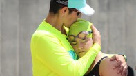 Man in a florescent long sleeve shirt is hugging a female swimmer.