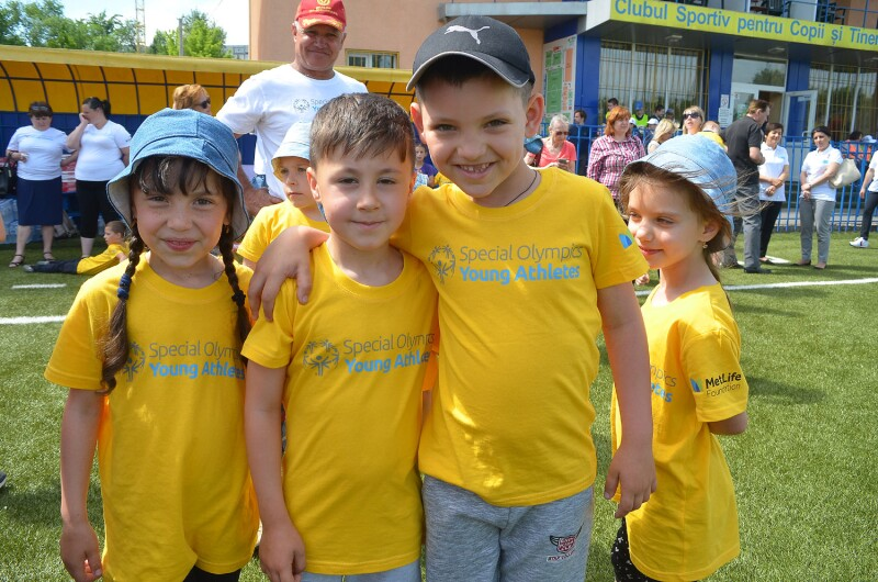 Three smiling young children in yellow Special Olympics Young Athletes t-shirts face the camera. They are standing on a grass pitch with a crowd behind them.