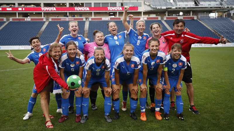 Slovakia female football team with coaches posing on the field for a group photo.