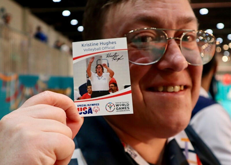 Kristine poses with her Special Olympics USA World Games trading card and smiles.